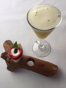 Van het huis: gin fizz met perzik. Amuse: uitgeholde aardbei met kokosmelk en munt.